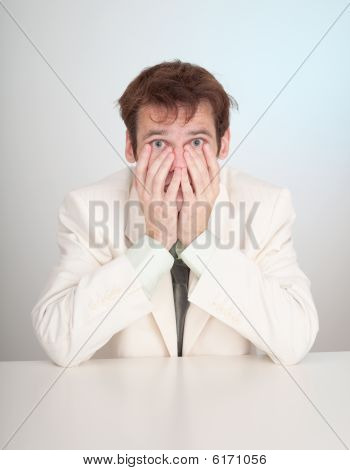 Young Sorrowful People In White Suit Sits At Table