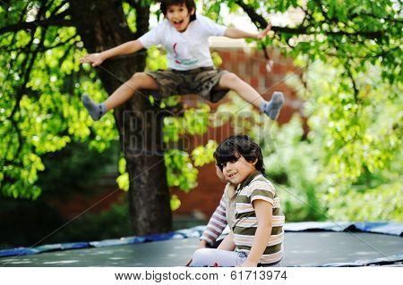Cheerful kids having fun jumping on trampoline