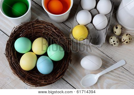 High angle view of Dying Easter Eggs. Dyed eggs in a nest with eggs in dye solution and other eggs ready to be dunked. Horizontal format.