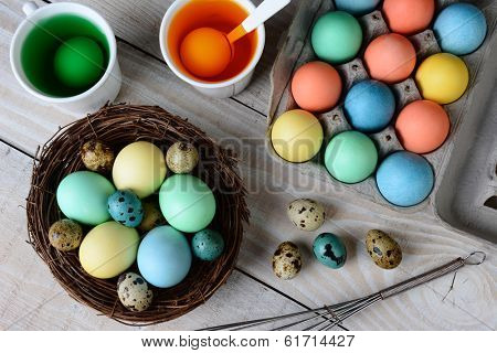High angle view of Easter Egg dying. Dyed eggs in a nest with eggs in dye solution. Horizontal format on a rustic farmhouse style kitchen table.