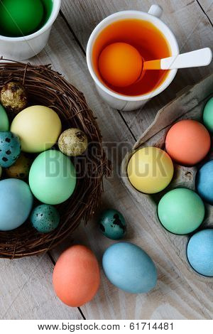 High angle view of Dying Easter Eggs. Dyed eggs in a nest with eggs in dye solution. Vertical format.