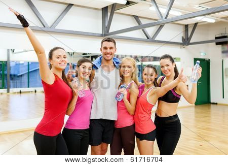 fitness, sport, training, gym and lifestyle concept - group of happy people with water bottles and towel in the gym waving hands