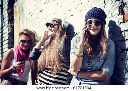 Girls having fun together outdoors and calling smart phone, lifestyle. Instagram effect.
