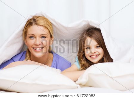 family, child and home concept - smiling mother and little girl under blanket at home