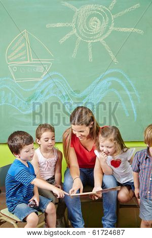 Children in preschool reading book together with a nursery teacher