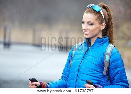 Closeup of young woman with Nordic walking poles in spring village