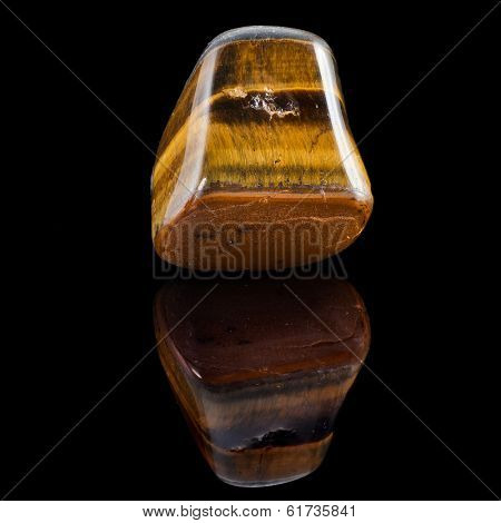 Tiger Eye mineral with reflection on black surface background
