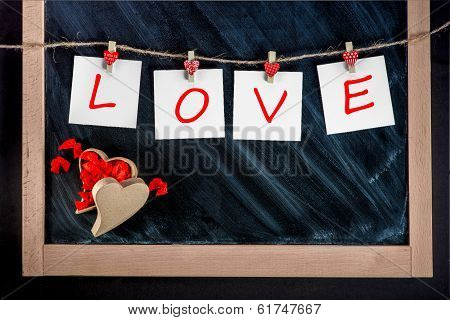 Paper Cards With Letters Love Attached With Clothes Pins On The Lace On The Chalkboard Background