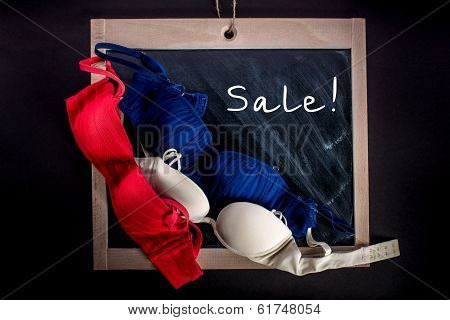 Three Brassieres Lying On The Chalkboard With The Word Sale