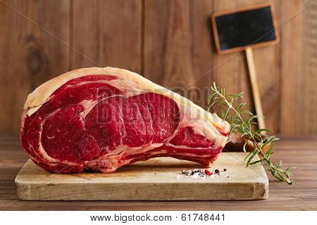 raw beef Rib bone  steak   on wooden board and table with empty black sign