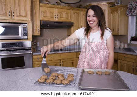 Woman Taking Cookies Off Pan