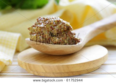 Traditional dijon mustard in a wooden spoon
