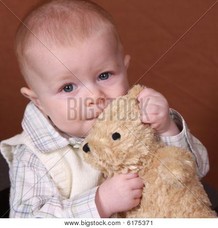 Adorable Baby Holding A Teddy Bear
