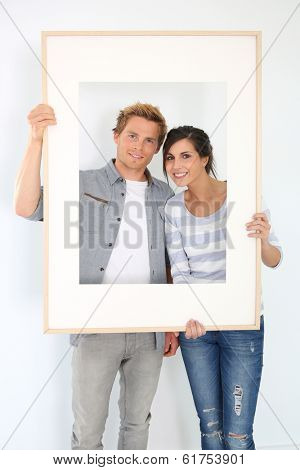 Cheerful young couple holding picture frame to look through