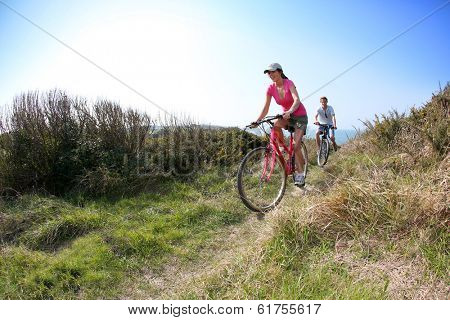 Couple riding bike on country path
