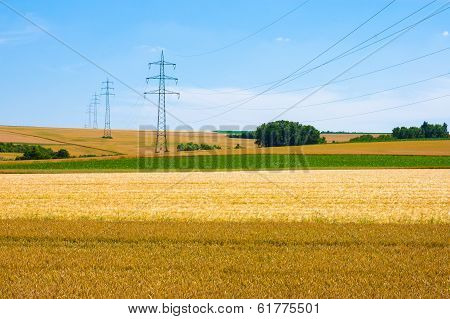 High-voltage Towers And Cables In Agricultural Fields On A Blue Sky Background.