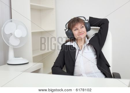 Woman Listens To Music In Ear-phones