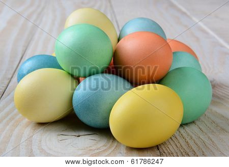 Closeup of a pile of pastel Easter Eggs on a rustic farmhouse style table. Horizontal format.