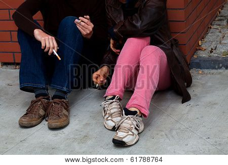 Smokers Sitting On Ground