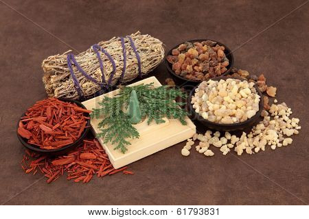 Frankincense, myrrh, sandalwood, incense cones , cedar leaf and smudge stick over lokta paper background.