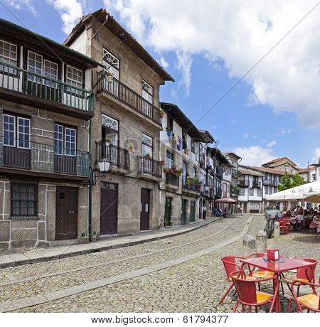Guimaraes, Portugal - April 25, 2013: People enjoy the esplanade in the Medieval Santiago Square, also known as Sao Tiago or Sao Thiago, in the Historical Center. Unesco World Heritage Site.