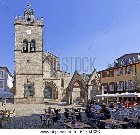 Guimaraes, Portugal - October 13, 2013: People enjoying the esplanades in the Oliveira Square with Nossa Senhora da Oliveira Church and Salado Monument in the background. UNESCO World Heritage Site.