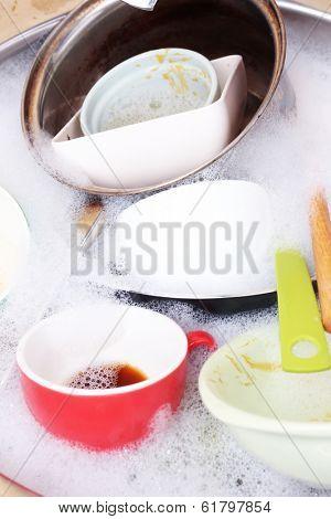 Utensils soaking in kitchen sink