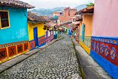stock photo of cobblestone  - Colorful colonial houses on a cobblestone street in Guatape Antioquia in Colombia - JPG