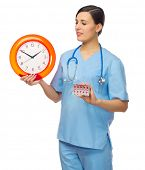 Doctor with clock and pills isolated