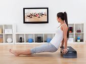 stock photo of bum  - Side view of an athletic barefoot young woman doing exercises in her living room while watching program or tape on television - JPG