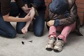 stock photo of heroin  - Three stoned drug addicts shooting heroin outdoors - JPG
