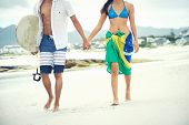 stock photo of board-walk  - Brasil latino hispanic couple walking holding hands with surfboard and flag as sarong - JPG