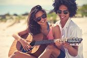 image of serenade  - Cute hispanic couple playing guitar serenading on beach in love and embrace - JPG