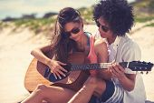 picture of serenade  - Cute hispanic couple playing guitar serenading on beach in love and embrace - JPG