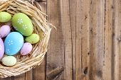 picture of wooden basket  - Easter eggs in nest on color wooden background - JPG