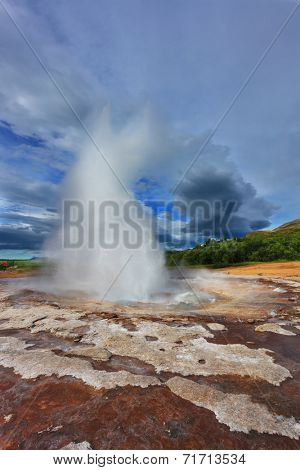 Gushing geyser Strokkur. High column of hot water and steam from the crater of the geyser. Iceland in the summer