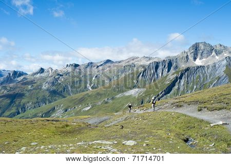 SEIGNE HILL, ITALY - AUGUST 27: Hikers on hill path with large peaks in the background. The region is a stage of the Mont Blanc tour, which crosses three countries. August 27, 2014 in Seigne Hill.