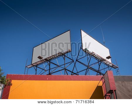 Two blank white billboards on rooftop against blue sky background.