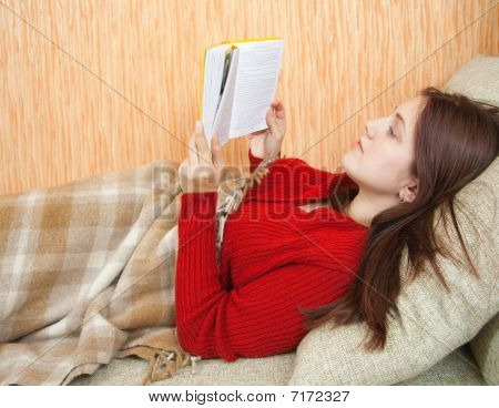 Pretty Young Girl Reading Book On Sofa