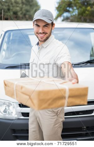 Delivery driver smiling at camera by his van offering parcel outside the warehouse