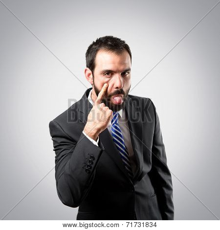 Young Businessman Making A Mockery Over Grey Background