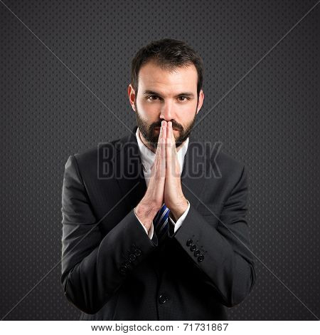 Young Businessman Pleading Over Black Background
