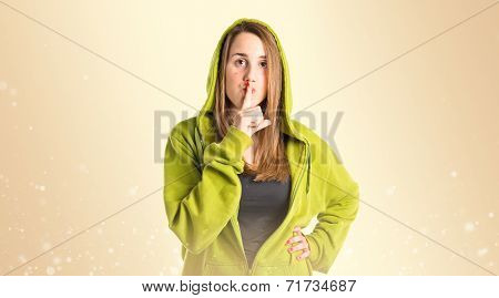 Young Girl Making Silence Gesture Over Ocher Background