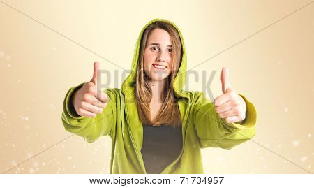 Pretty Young Girl With Thumbs Up Over Ocher Background