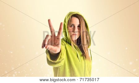 Girl Doing Victory Gesture Over Ocher Background