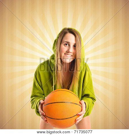 Blonde Girl Playing Basketball Over Ocher Background