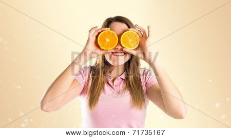 Girl With Oranges In Her Eyes Over Ocher Background