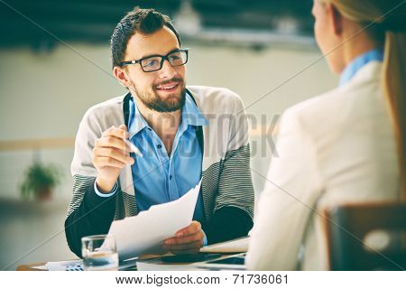 Smiling businessman with papers consulting his colleague at meeting