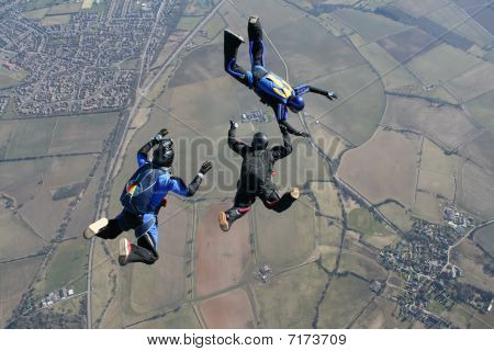 Camera man films two skydivers in freefall