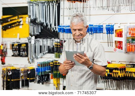 Smiling senior customer holding digital tablet in hardware shop